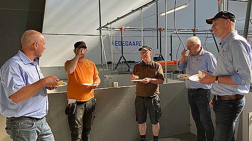 Cinq hommes mangent et boivent dans le bâtiment et discutent.