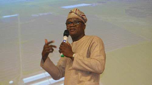 Le professeur Adesehinwa portant un microphone